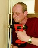 Mid-adult man drilling hole in the wall. Closeup concept. Mid-adult man drilling hole in the wall. Closeup concept Stock Photo