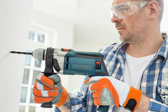 Mid-adult man drilling hole in wall. Mid-adult men drilling hole in wall Stock Photo