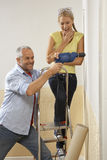 Mid adult man drilling into a wall with a young woman standing on a step ladder Stock Photo