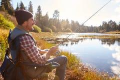 Mid-adult man fishing by lakeside, Big Bear, California, USA royalty free stock photo