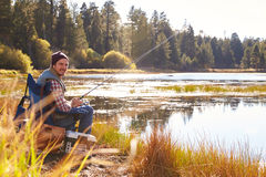 Mid-adult man fishing by lakeside, looking to camera Royalty Free Stock Photo