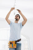Mid-adult man fixing light bulb wiring in new house Royalty Free Stock Photo
