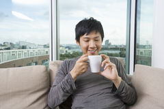 Mid adult man holding coffee cup in house Royalty Free Stock Photos
