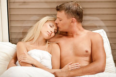 Mid adult man kissing girlfriends's forehead Royalty Free Stock Photo