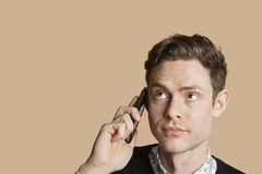 Mid adult man listening to mobile phone over colored background Stock Images