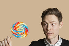 Mid adult man looking at lollipop over colored background Stock Photos