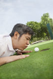Mid adult man lying down in a golf course trying to blow the ball into the hole Royalty Free Stock Images