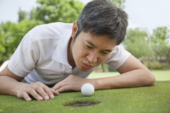 Mid adult man lying down in a golf course trying to blow the ball into the hole Stock Image
