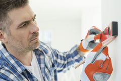 Mid-adult man marking on wall with level stock photography