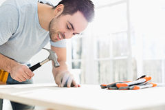Mid-adult man nailing in table Royalty Free Stock Images