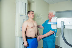 Mid adult man patient mature male doctor setting up the machine to take x-ray royalty free stock photo