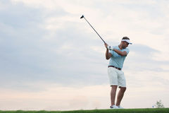 Mid-adult man playing golf against sky Royalty Free Stock Photography