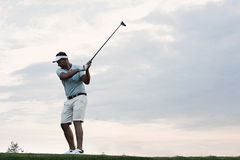 Mid-adult man playing golf against sky Stock Photography