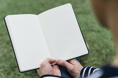 Mid adult man reading blank book in garden royalty free stock image