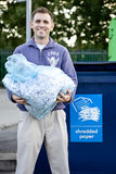 A mid-adult man recycling a bag of shredded paper Stock Images