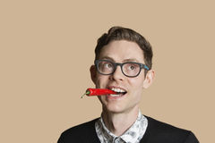 Mid adult man with red chili pepper while looking away over colored background Royalty Free Stock Images