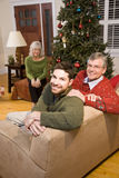 Mid-adult man and senior parents by Christmas tree Royalty Free Stock Image