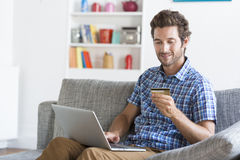 Mid adult man shopping using laptop and credit card in modern apartment Stock Images