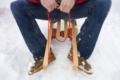 Mid adult man sitting on sled in snow, cropped view Stock Photos