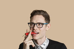 Mid adult man smoking red chili pepper over colored background Stock Images