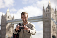 A mid-adult man taking a photograph of himself in front of Tower Bridge Stock Photography