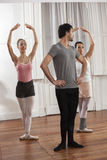 Mid Adult Man Training Ballet Dancers In Studio Stock Images