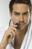 Mid adult man using nose hair trimmer Stock Image