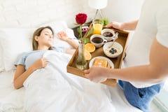 Man Bringing Healthy Breakfast For Sleeping Girlfriend In Bed. Mid adult men bringing healthy breakfast for sleeping girlfriend in bed at home Stock Photo