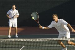 Mid Adult Men Playing Tennis Royalty Free Stock Photos