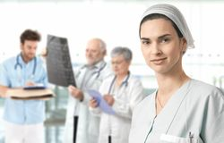 Mid-adult nurse with medical team in background Stock Image