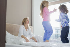 Mid adult parents looking at playful children in bedroom Royalty Free Stock Photography