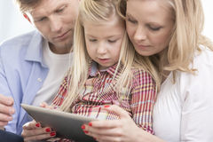 Mid adult parents using tablet PC with daughter at home Stock Image