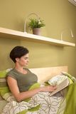 Mid-adult pretty woman reading in bedroom Royalty Free Stock Photo