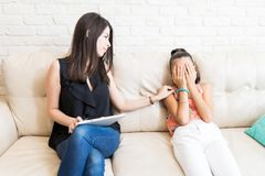 Psychologist Consoling Sad Girl Covering Face On Sofa. Mid adult psychologist consoling sad girl covering face on sofa at home stock photos