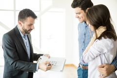 Realtor Showing Blueprint To Couple In New Apartment royalty free stock photo