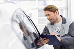 Mid adult repair worker writing on clipboard while examining car in workshop Royalty Free Stock Photos