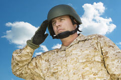 Mid-adult soldier in military uniform saluting against cloudy sky Royalty Free Stock Images