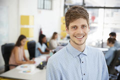 Mid adult white man smiling to camera in an open plan office Stock Images