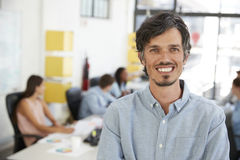 Mid adult white man smiling to camera in an open plan office Royalty Free Stock Photo
