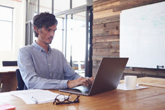 Mid-adult white man working in an office using laptop Stock Photography
