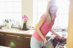 Mid adult woman baking cookies in kitchen Royalty Free Stock Photography