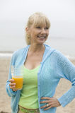 Mid-adult woman on beach holding a glass of orange juice Stock Image
