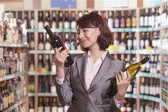 Mid Adult Woman Choosing Wine in a Liquor Store Royalty Free Stock Photo