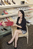 Mid adult woman customer taking footwear box from female salesperson Stock Photo