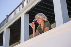 Mid adult woman drinking red wine while standing in balcony at restaurant Royalty Free Stock Image