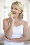 Mid Adult Woman Eating Green Apple Stock Image
