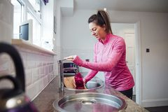 Filling my Bottle for the Gym. Mid adult woman is filling her reusable water bottle at home before she goes to the gym royalty free stock images