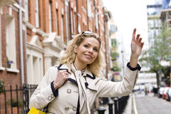 A mid adult woman hailing a taxi Stock Photography