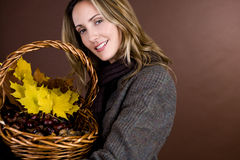 A mid adult woman holding a basket of conkers, acorns and autumn leaves Royalty Free Stock Photos