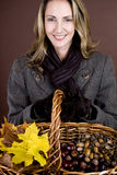 A mid adult woman holding a basket of conkers, acorns and autumn leaves Stock Image